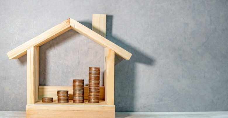Coins-stacked-in-wooden-house-frame-on-table.-Home-mortgage-loan-rate.-cm